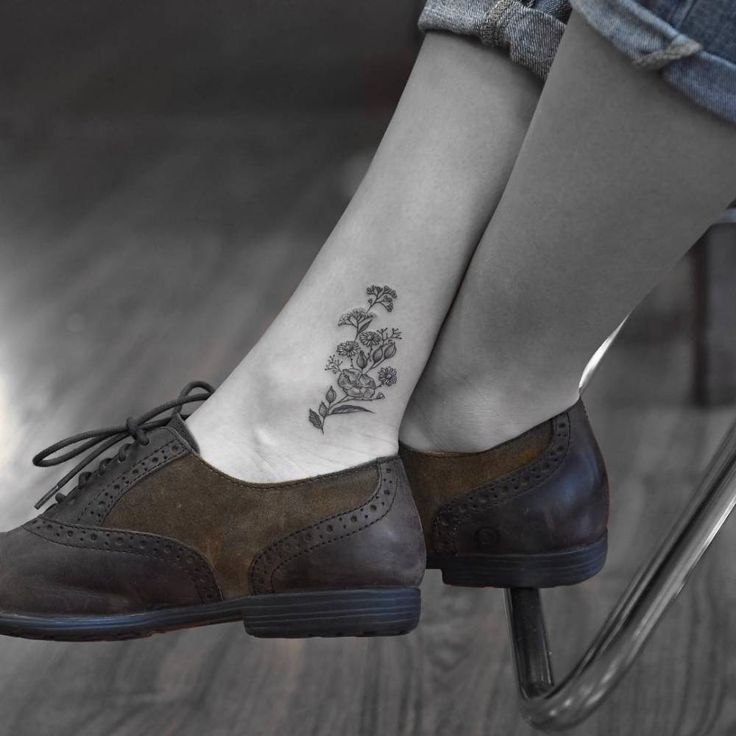 Flowery black ankle tattoo