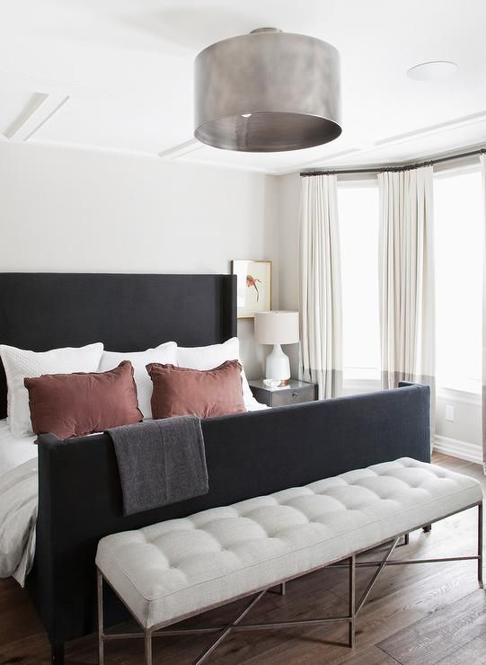 Contemporary bedroom features a metal drum semi flush mount light illuminating a black wingback bed with footboard dressed in rust shams flanked by metal nightstands alongside a white linen tufted bench placed at the foot of the bed next to a bay window dressed in gray banded curtains.