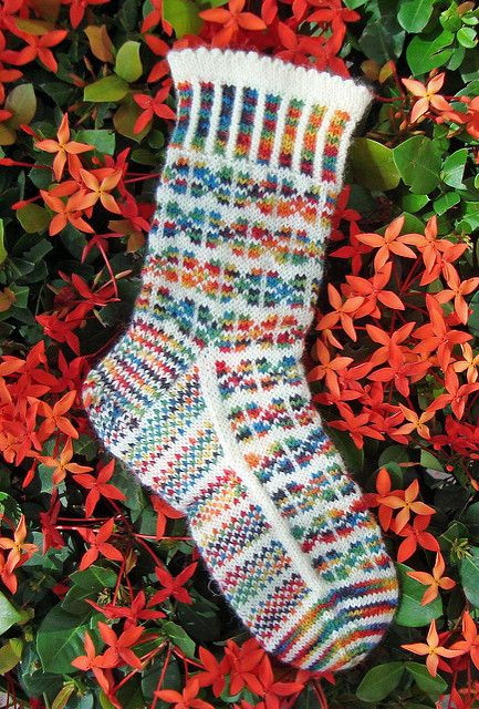 Tiny flowers decorate this sock in a pattern reminiscent of patchwork quilts or a field of flowers. When choosing yarns it would be best to use a solid color that does not have any of the colors in the multi-colored yarn so that the motifs stand out better. Sock is constructed from the top down with picot hemmed & corrugated ribbing cuff and traditional heel flap & gusset shaping at the ankle.