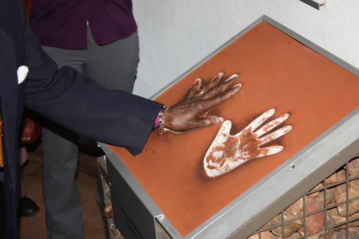 Archbishop Emeritus Desmond Tutu places his hand in the hand prints of Nobel laureate, former South African president Nelson Mandela. He visited Maropeng on July 31 2013.