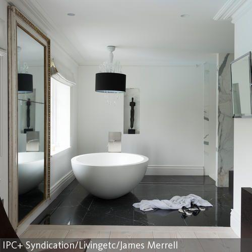 In diesem Badezimmer befindet sich eine ausgefallene freistehende Badewanne. Der schwarze Marmorboden komplementiert den luxuriösen Look und ein sehr großer…