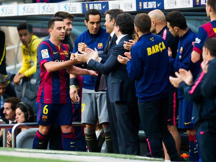 Xavi saluda a sus compañeros del banquillo