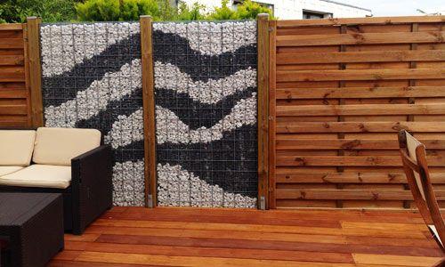 Création d'une cloture palissade en bois et pierres de couleurs