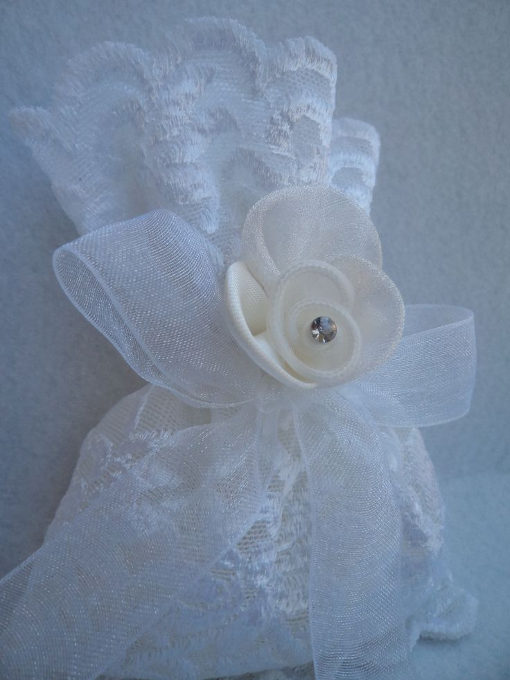 Pouch made of white lace and decorated with  an organtza ribbon and a fabric flower.