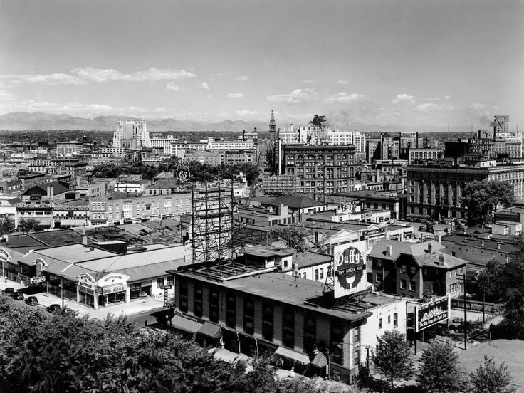 Denver in the 1940s looking northwest from the State Capitol. Signs and businesses in this picture include Walker Buick Used Cars, Tours Hotel, Duffy's Dry Ginger Ale, Shirley Savoy Hotel, Hotel Cory, Broadway Hotel, Harley Davidson, Pennsylvania Tires, QRS Neon, Denver Theatre, Phillips 66, Mobilgas and Conoco.