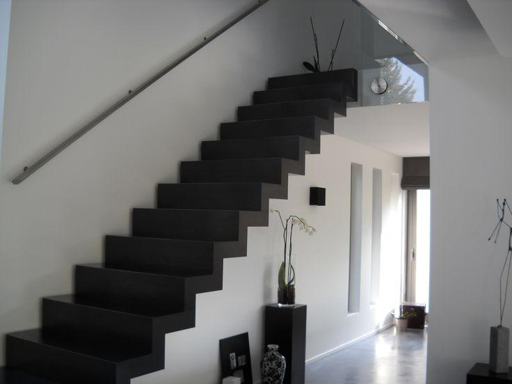 Zwarte design trap staal met strakke leuning langs de muur.
