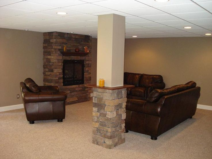 I like this basement with the gas fireplace surounded by stacked stone, and the cool idea for hiding the column with stone and a shelf for beverages. Nice!