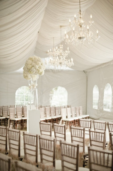 Pure white topiaries and chandeliers give this simple tent an understated, chic atmosphere