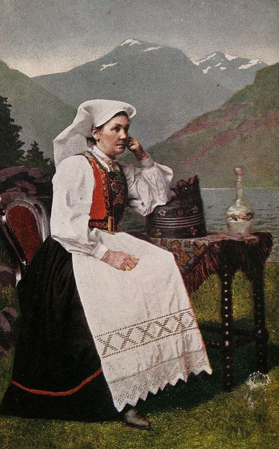 Norwegian Woman in her national Costume. Shows her in a Norwegian setting. Norwegian postcard, circa 1900 - 1920.