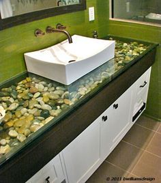 "1"" glass counter-top with river rock fill. Love the green stained walls.  (Get rid of the green, replace with a round bowl type sink - river rock/glass only goes out 6-8 inches on either side and replace the rest of the counter top with wantbto make a shadow box table like this granite)"