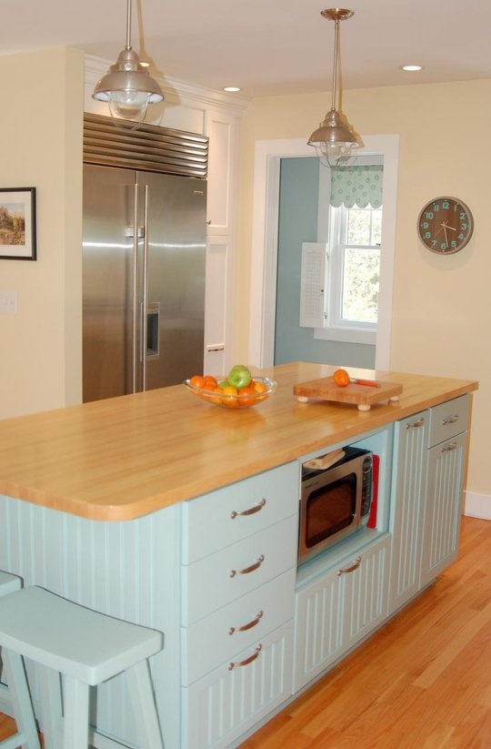 blue & yellow kitchen with microwave in island