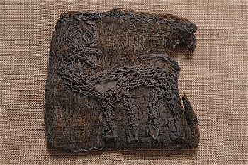 Viking era textile fragment with embroidery depicting a deer looking backwards