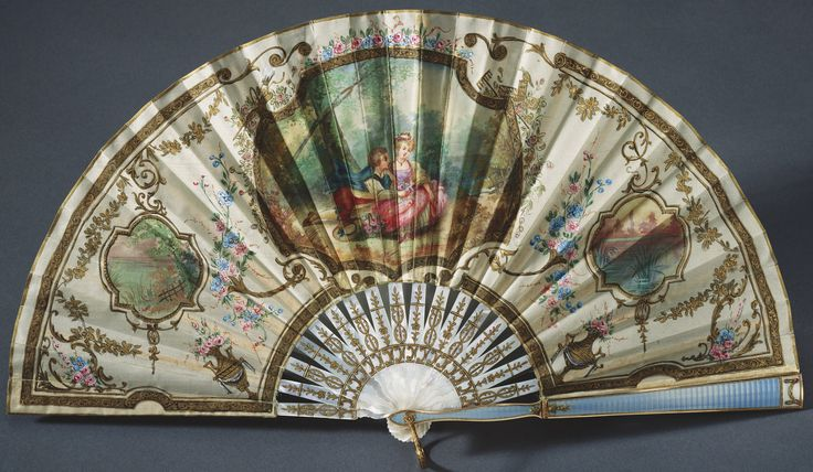 Queen Mary's Fabergé fan, by workmaster Henrik Emanuel Wigström c. 1912. Plain weave cream silk leaf, backed with silk gauze; front guard of mother-of-pearl with two-colour gold enamelled in blue and white over a guilloché ground, decorated with two Burmese cabochon rubies; back guard and sticks of mother-of-pearl. Provenance: purchased from Fabergé's London branch by Queen Alexandra, 24 December 1912 as a gift for Queen Mary.