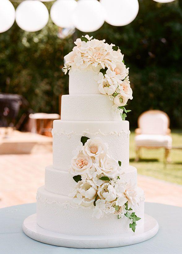 Elegant 5 tier wedding cake decorated with sugar flowers. White wedding cake, outdoor wedding cake