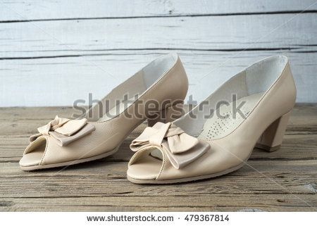 Pair of high heel woman shoe on old wooden table