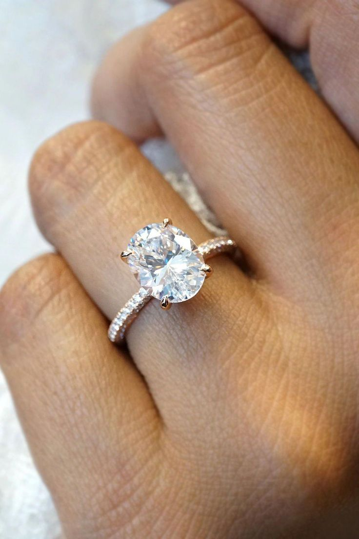 This dazzling engagement ring features an oval diamond in a rose gold talon pron…