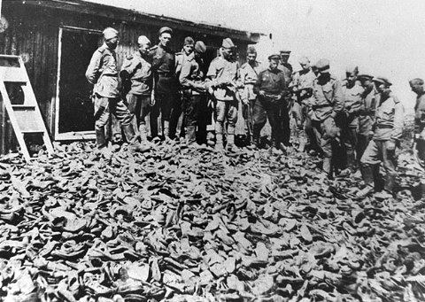 Soviet soldiers investigating Majdanek survey a warehouse containing thousands of shoes confiscated from murdered prisoners.