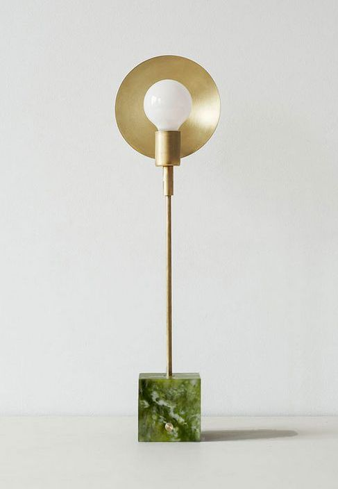 Cette lampe de table dispose d'un disques de laiton autour d'une ampoule avec une base disponible en trois variétés de pierre, Carrara, marbre vert et travertin.