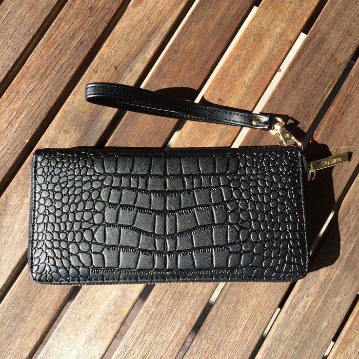 Deze zwarte portemonnee met kroko reliëf en polsbandje is 21 x 10 cm. Aan de binnenkant is deze bordeaux rood. Ook te gebruiken als clutch.