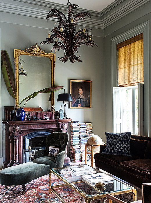 Moody and romantic library with a gold mirror, velvet bench, oil painting, crown mouldings and dramatic brass chandelier.