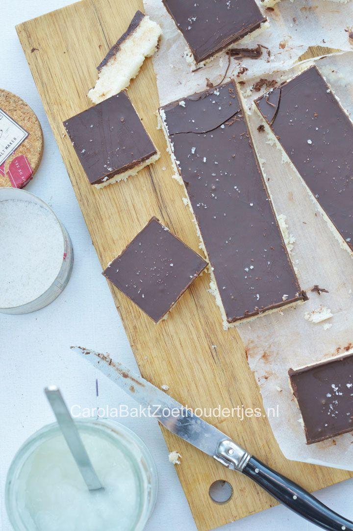 200 gr geraspte kokos, 1 blikje gecondenseerde melk, 5 el kokosolie, snufje zout, snufje fleur de sel, 1 tl vanille extract, 200 gram pure chocolade. Mix de ingrediënten, behalve de chocolade en de fleur de sel voor bovenop door elkaar. Laat je kokoskoek een goed uur vriezen. Verwarm de chocolade au bain marie en giet dit over de koek, de chocolade zal sneller afkoelen dan normaal. Strooi eventueel wat fleur de sel over de koeken.