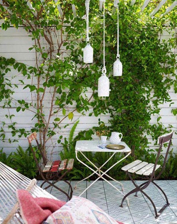 Een witte schutting en smalle groenstrook geeft een smalle tuin meer ruimtegevoel