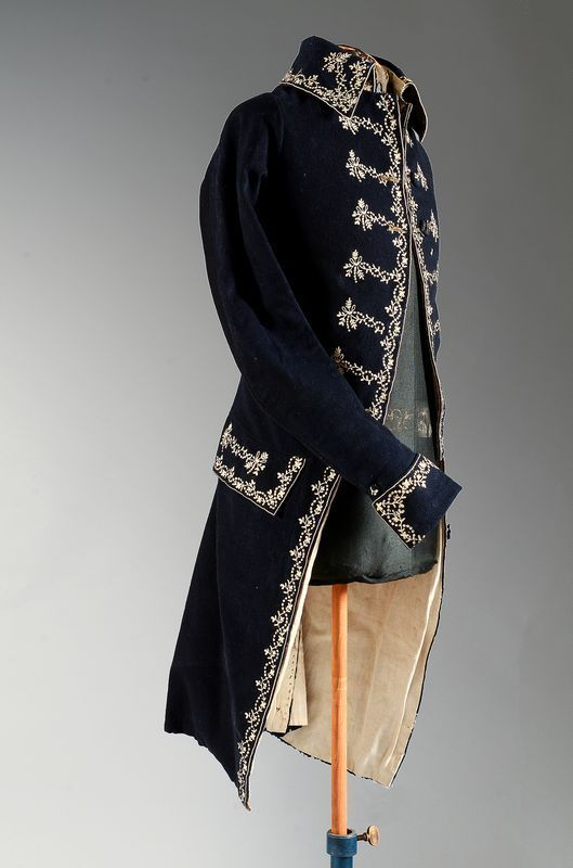 Coat, probably France, late 18th century. Navy blue wool embroidered with small floral festoons in multicoloured silk threads.