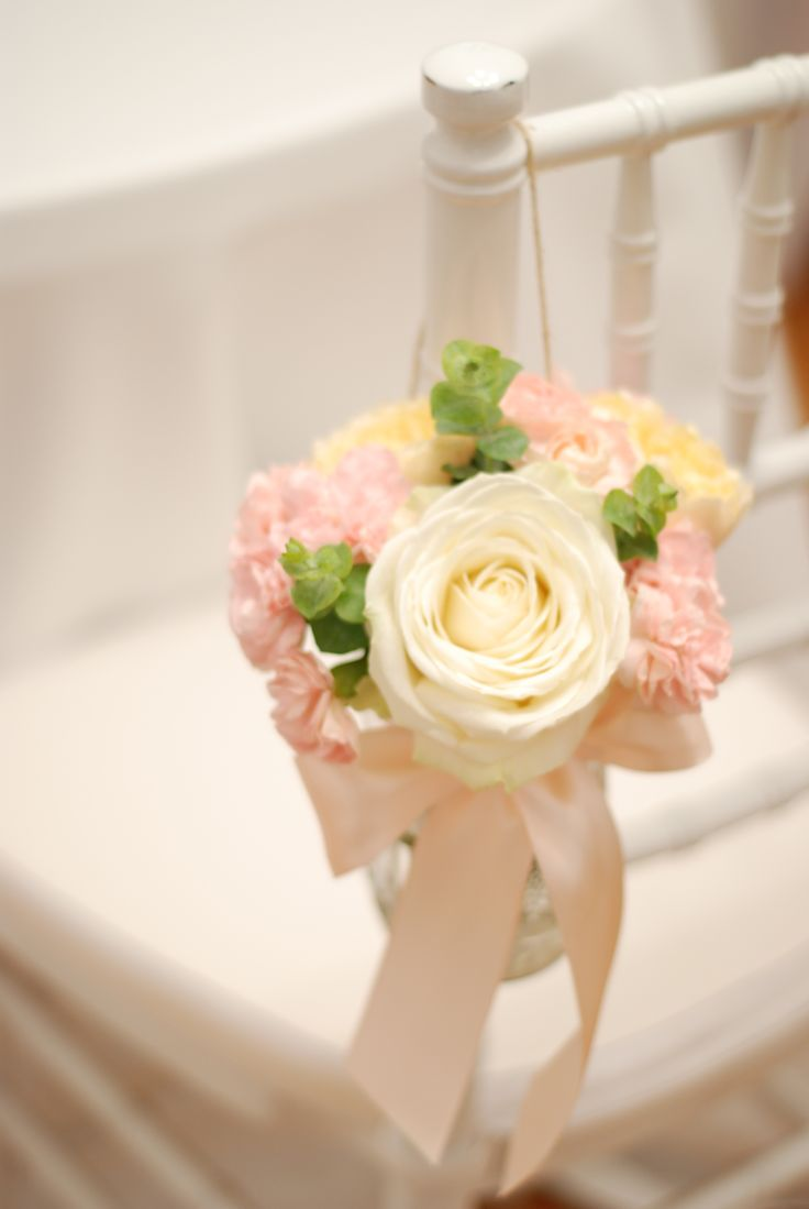 Beautiful flowers in mason jars as wedding chair decoration for a spring or summer wedding