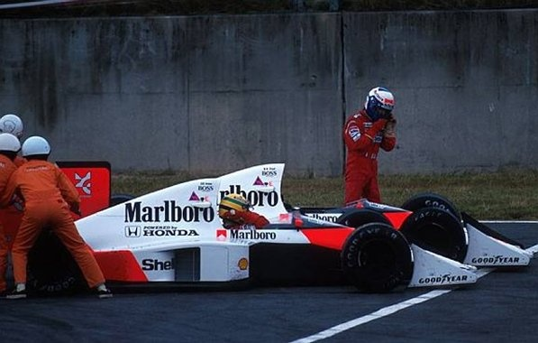 Alain Prost (FRA) McLaren MP4/5 walks from his car following a collision with team mate Ayrton Senna (BRA) at the entrance to the chicane. Meanwhile Senna pleads with the marshals to push start him. They did, he recovered to win, but was disqualified. Formula One World Championship, Japanese Grand Prix, Suzuka, Japan. 22 October 1989.