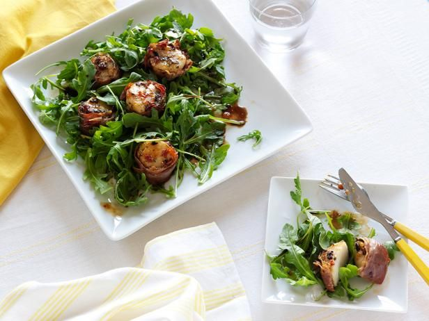 Prosciutto-Wrapped Scallops : Giada De Laurentiis first coats scallops in a pesto of sun-dried tomatoes, basil and black olives, then she wraps them in slices of prosciutto. After the scallops are baked, they're served atop an arugula salad.