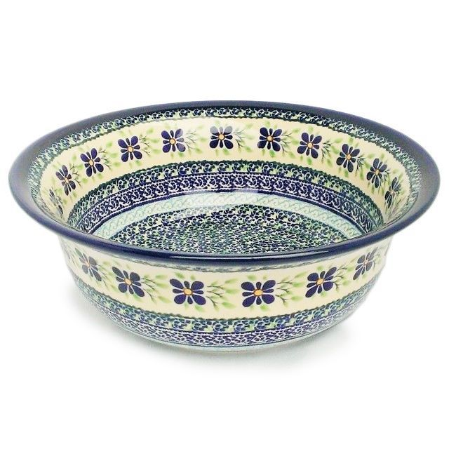 Dish out soups, salads, sides and more with this exquisite Polish stoneware bowl. This serveware piece is artisan-crafted of durable ceramic with a high fired glaze boasting an intricately painted motif in blue and green tones.