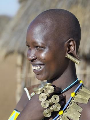 Africa | A Datoga woman in jovial mood in Northern Tanzania. The traditional attire of Datoga women includes beautifully tanned and decorated leather dresses and coiled brass armbands, necklaces, earrings and rings. Yellow and light blue are the preferred colors of the beads they wear. Scarification of the face is not uncommon among women and girls. | © Nigel Pavitt