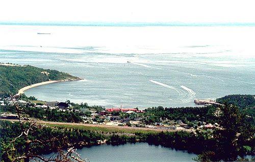 RN - Tadoussac. Situé au confluent du fleuve St-Laurent et de la rivière Saguenay et faisant partie de la région administrative de la Côte-Nord, le village de Tadoussac compte aujourd'hui environ 843 habitants. Porte d'entrée du comté de la Haute-Côte-Nord et situé sur la route des baleines dans la région touristique de Manicouagan, ce petit hameau déborde d'activités et de vie grâce à ses événements reconnus et à la richesse de son patrimoine.