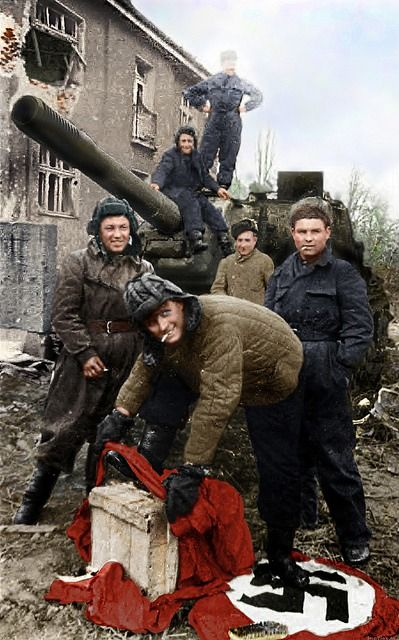 "Lieutenant Tovolzhansky wipes his boots with Nazi flag at ACS ICS-152 ""Deerslayer"" on the street of Breslau, 1945."