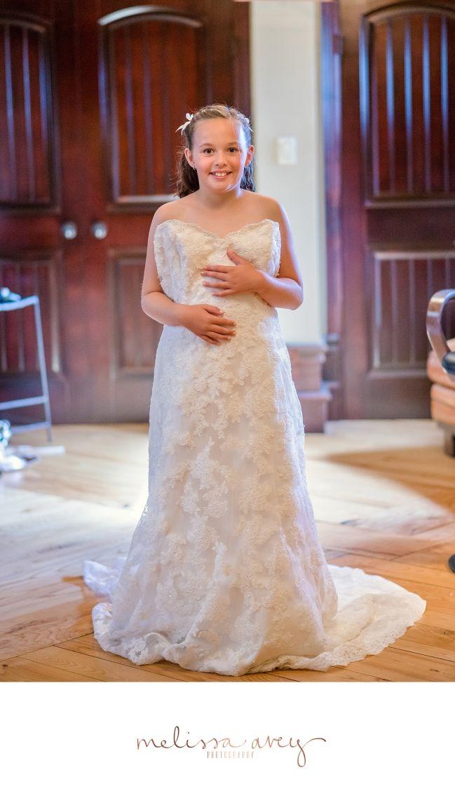 Little girl trying on bride's dress   Hacienda Sarria Wedding   Melissa Avey Photography