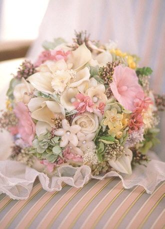 Calla lilies, hollyhocks, freesis, stephanotis jasmine, roses, jonquils with accents of heather and hydrangea create this bouquet named Magnificent. Flowers are all garden grown.