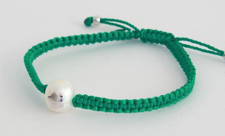 Pulsera tejida en macramé de color verde, con flor sobre perla blanca.