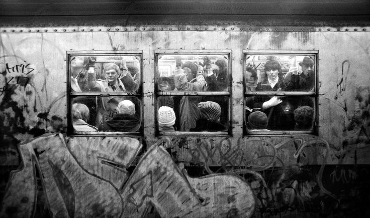 1981, A subway car full of passengers inside, and graffiti outside.