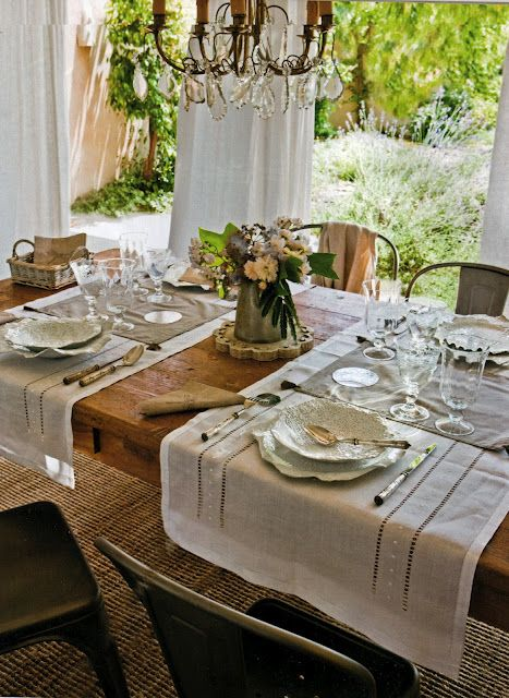 Such an inviting table!  A bit rustic with a fancy chandelier, linen runners with pretty dishes and glasses, a sweet bouquet of flowers, and a relaxing view outside huge windows.