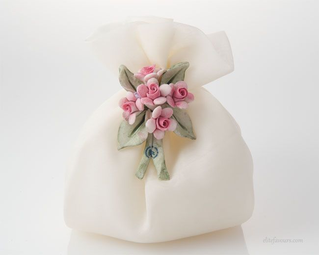 Finest quality organza sachet filled with almond confetti candies and soft filling, hand made Capodimonte ceramic flower composition.