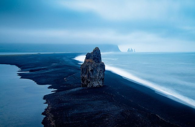A volcanic sandy beach leads up to the Dyrholaey fingers along the east coast of Iceland