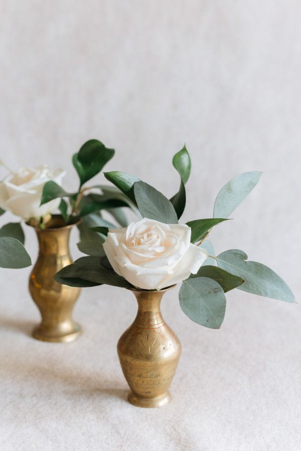 A trio of gold bud vases filled with a mix of dusty blush Quicksand roses, light blue delphinium, ivory spray roses, white astilbe, silver dollar eucalyptus, and olive branches