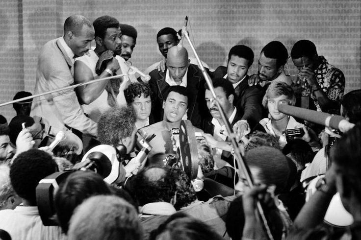 """TO GO WITH AFP STORIES In this photo taken on October 30, 1974 shows US boxing heavyweight champion Muhammad Ali (C) (born Cassius Clay) during a press conference after the heavyweight world championship in Kinshasa. On October 30, 1974 Muhammad Ali knocked out George Foreman in a clash of titans known as the """"Rumble in the Jungle"""", watched by 60 000 people in the stadium in Kinshasa and millions elsewhere AFP PHOTO"""