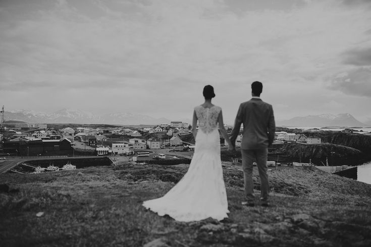 Bride and groom holding hands watching over Stykkishólmur, Iceland. Eloping in Iceland: http://johannahietanen.com/wedding/iceland-wedding-photographer-e-z/