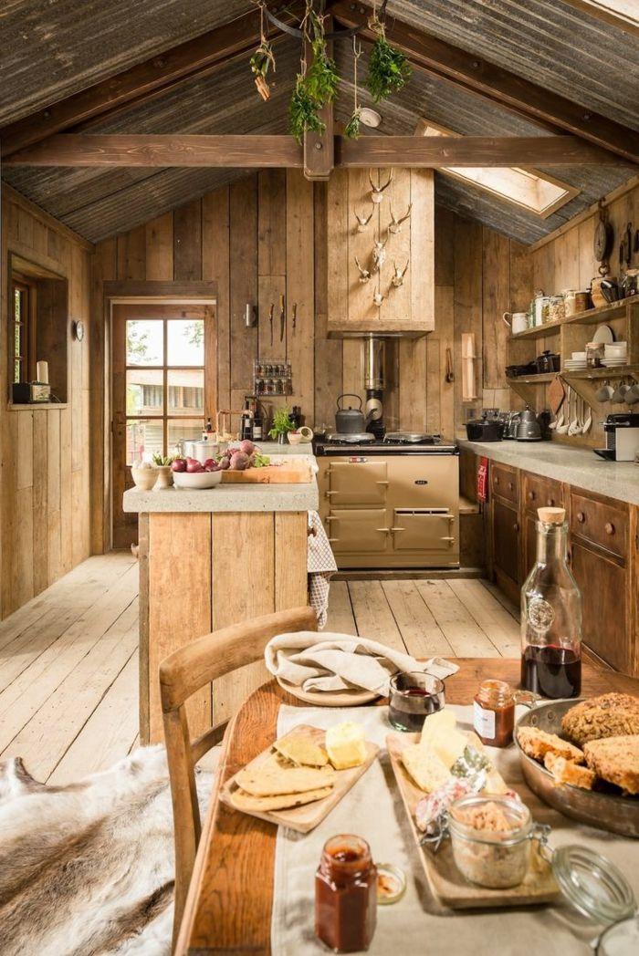 cocinas con encanto, cocina de madera rústica con isla, techo con vigas, mesa con quesos, decoración cabezas de ciervo