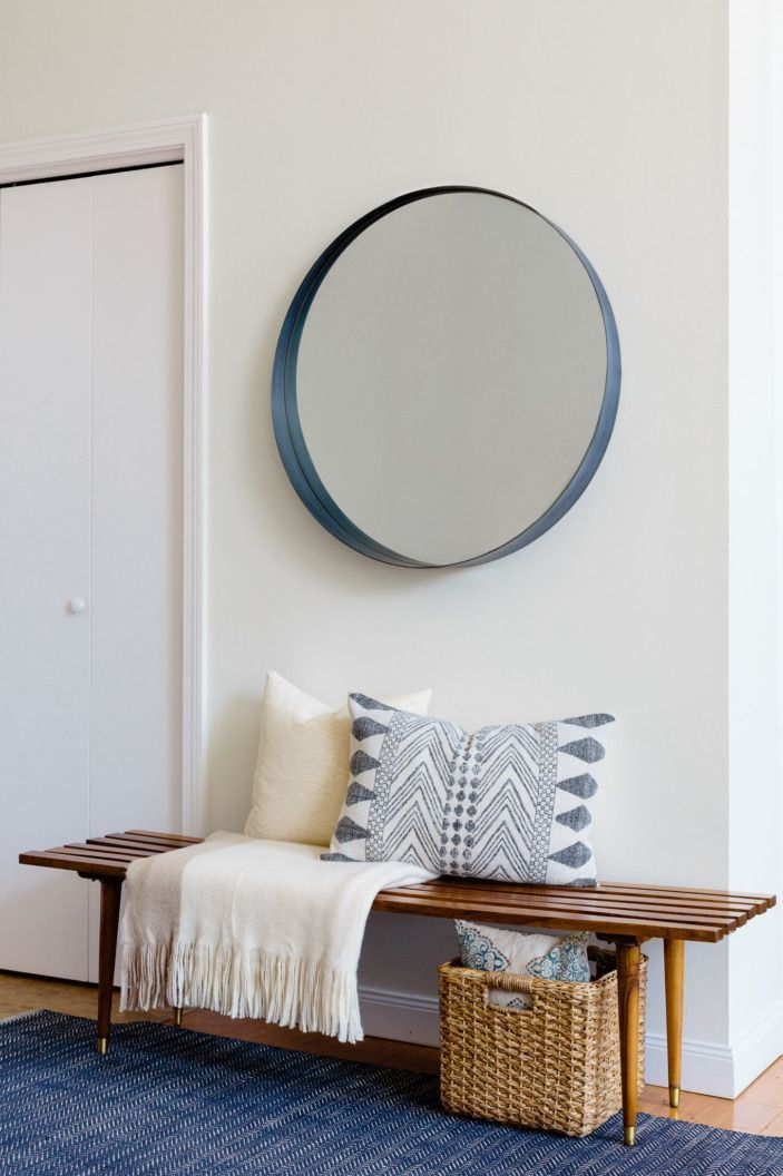 In the entryway, a rounded mirror hangs above a midcentury modern slatted bench. It was a find at a local vintage shop.