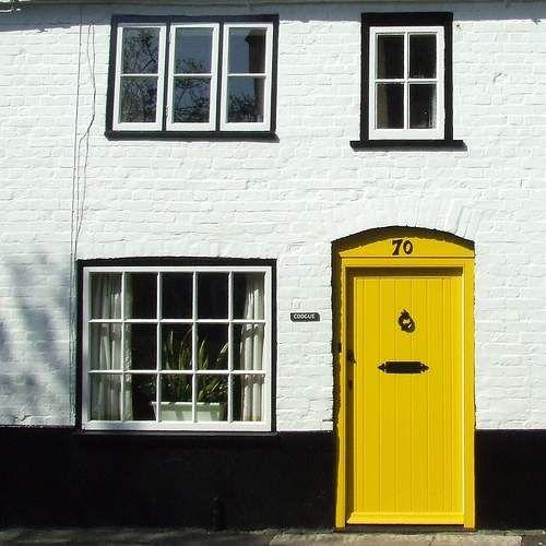 White brick, black foundation, yellow door. Good.