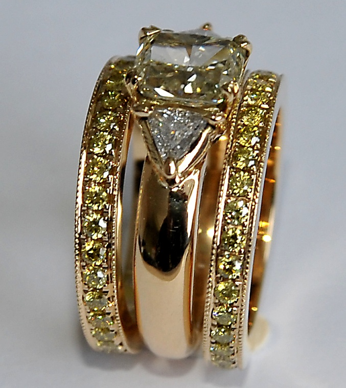 OMG!!!!!18 karaats gouden ring, met champagnekleurige diamant en twee triljanten. De ring wordt geflankeert door twee alliances, gezet met groen/gele briljant