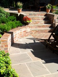 Brick garden steps with brick coping. Stone paving and pine and pachysandra planting at a garden in Leeds by Paperbark Garden Design