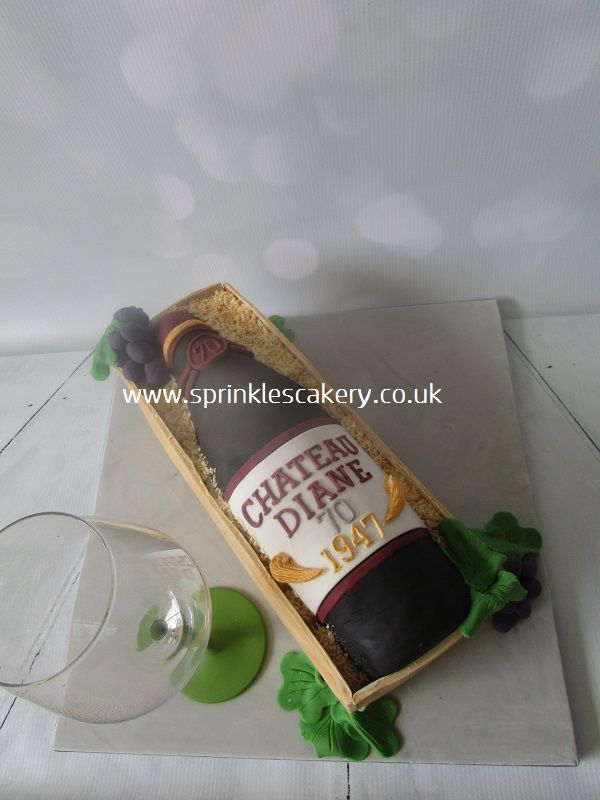 "This bottle of wine cake was carved from a 12""x8"" tin and 'built' to be the same size as a 75cl bottle of wine in a display box made from fondant and finished with desiccated coconut."